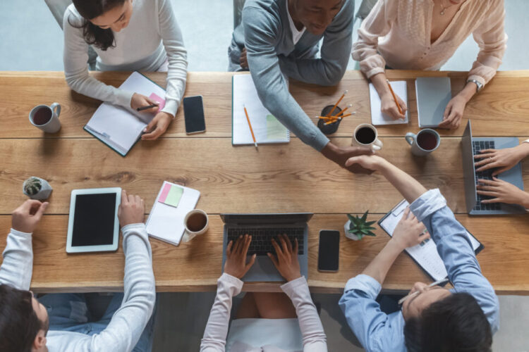 Top view of colleagues shaking hands during group business meeting