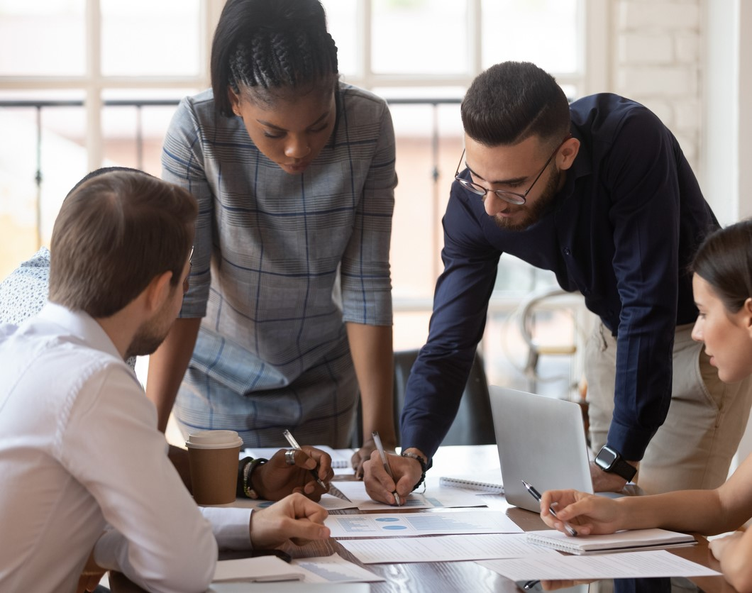 Focused multiracial corporate business team people brainstorm on marketing plan financial report gather at office table meeting, diverse serious colleagues group discuss paperwork engaged in teamwork